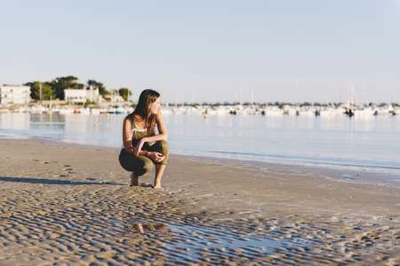 cowering: France, Pornichet, woman crouching on the beach at sunset