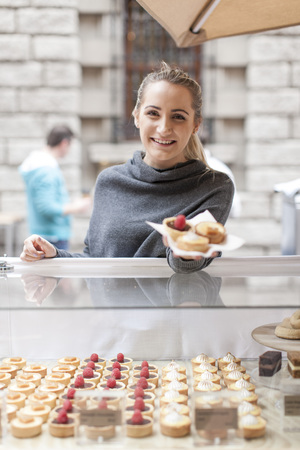 selling service: Young woman selling pastries at market