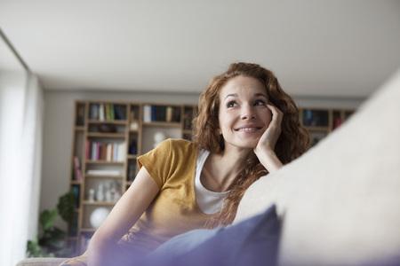 Mujer sonriente en casa sentado en el sofá