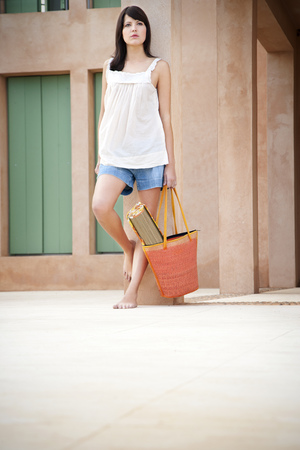 Young woman with bag and beach mat leaning against pillar