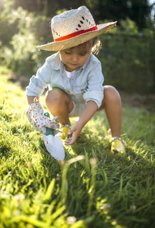 cowering: Little girl crouching with gardening glove and hand trowel on a meadow