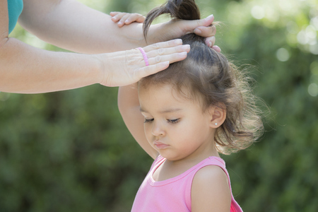 Mother tying hair of her little daughter