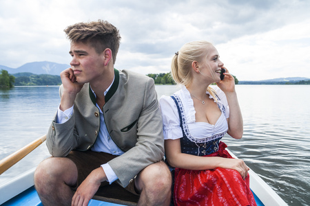 irrespeto: Germany, Bavaria, young couple wearing traditional clothes sitting in a rowing boat on Staffelsee