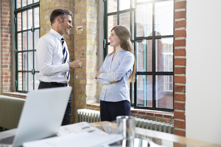 Mature man and woman talking in office