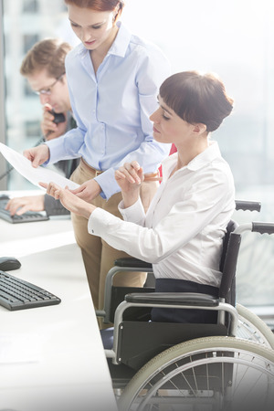 Woman in wheelchair and two colleagues working in office