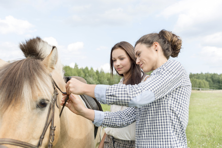 Young woman showing teenage girl how to fasten bridle LANG_EVOIMAGES