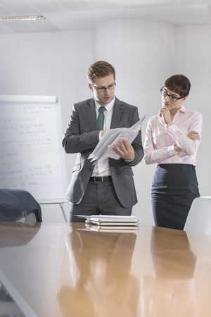 Businessman and businesswoman discussing document in conference room