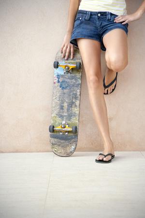 sandalias: Piernas de mujer joven con longboard frente a una pared