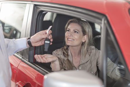 Woman sitting in new car receiving key