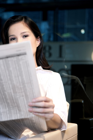 obscuring: Young businesswoman sitting in armchair reading newspaper LANG_EVOIMAGES