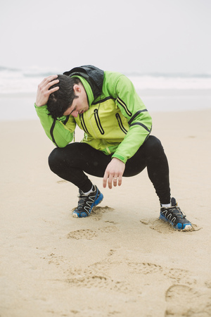 cowering: Spain, Valdovino, exhausted young man after jogging on the beach at rainy day