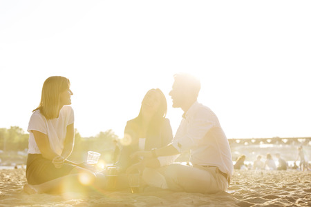Three happy friends sitting on city beach having a beer