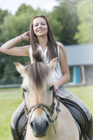 Portrait of smiling teenage girl riding on a horse