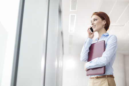 Businesswoman on the phone at office window