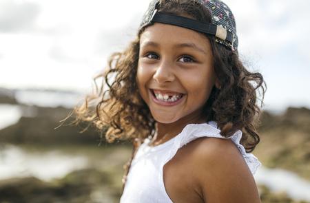 pelo castaño claro: España, Gijón, retrato de la niña sonriente con el espacio del diente en la costa rocosa LANG_EVOIMAGES