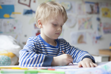 Portrait of blond little boy painting with crayon LANG_EVOIMAGES