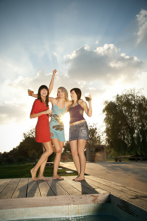 feet naked: Three happy young women having a party at the poolside LANG_EVOIMAGES