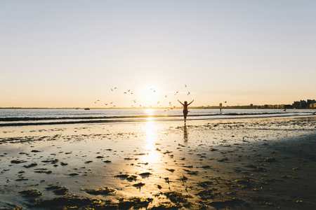 France, Pornichet, silhouette of running woman on the beach at sunset LANG_EVOIMAGES
