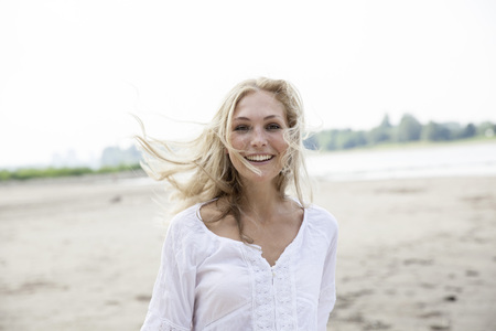 hait: Portrait of smiling blond woman with blowing hait on a beach LANG_EVOIMAGES