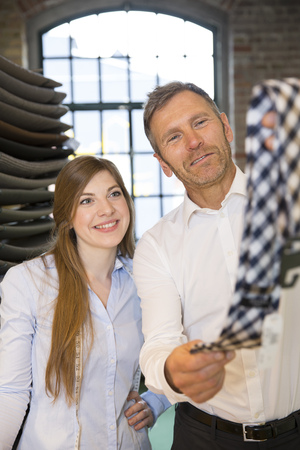Young woman helping customer to choose tie