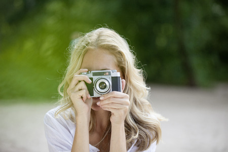 vintage: Blond woman taking a photo with an old camera