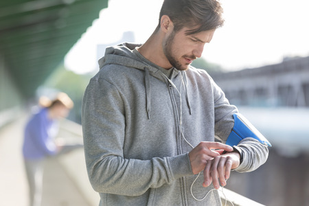 self testing: Young athletic man checking his watch