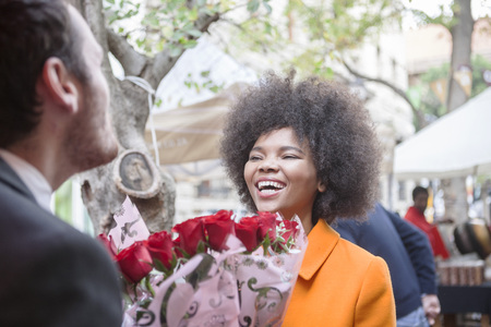 incidental people: Man buying red roses for a woman