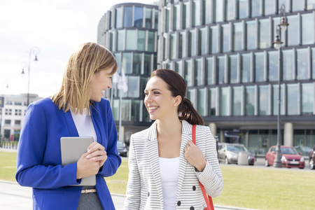 Two smiling business colleagues outdoors