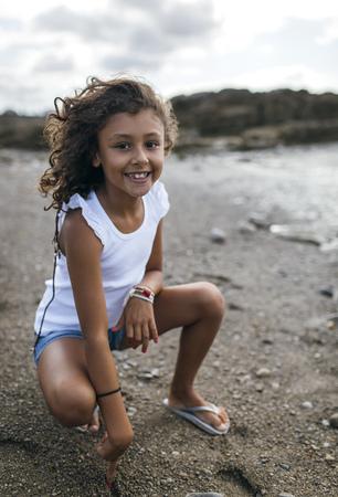 sandalias: España, Gijón, retrato de la niña sonriente que se agacha en la playa