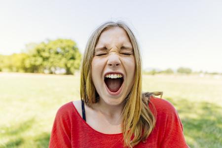 Portrait of teenage girl outdoors screaming