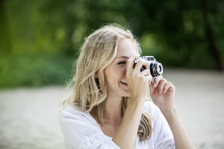 vintage: Smiling blond woman taking a photo with an old camera