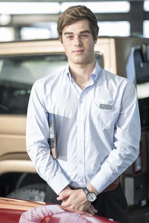 selling service: Portrait of confident car dealer in showroom LANG_EVOIMAGES
