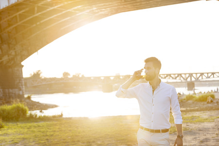 Man having a beer by the riverside