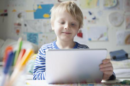 only boys: Portrait of smiling little boy using digital tablet