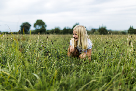 cowering: Girl crouching on a meadow LANG_EVOIMAGES