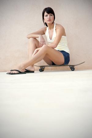 sandalias: Retrato de mujer joven sentada en su longboard