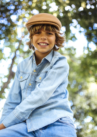in low spirits: Portrait of smiling blond boy wearing cap