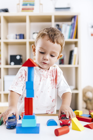 Portrait of excited little boy playing with building bricks and toy cars