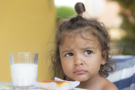 Portrait of unhappy little girl with breakfast