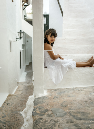 Spain, Balearic Islands, Menorca, Binibeca, portrait of little girl sitting on a step LANG_EVOIMAGES
