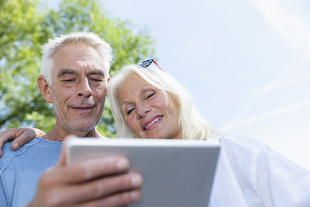 Senior couple looking at digital tablet outdoors