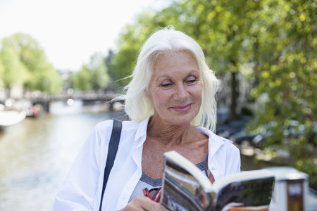 Netherlands, Amsterdam, smiling senior woman reading tour book at town canal