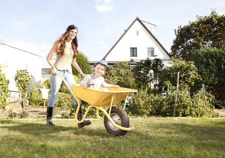 Woman with her little son sitting in a wheelbarrow