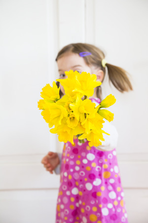 Little girl showing bunch of daffodils