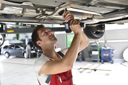 Car mechanic working in repair garage, repairing unterbody
