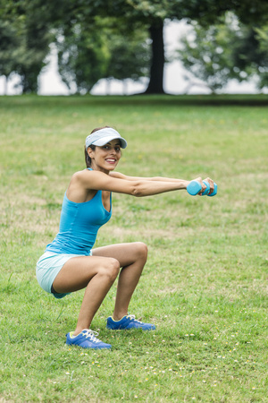 cowering: Young woman working out in park