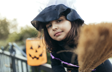 Portrait of little girl masquerade as a witch with halloween lantern and broom LANG_EVOIMAGES