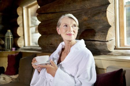 Smiling senior woman in bathrobe drinking tea