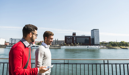 Two young businessmen walking by the riverside LANG_EVOIMAGES