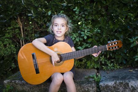 plucking: Spain, girl playing spanish guitar outdoors